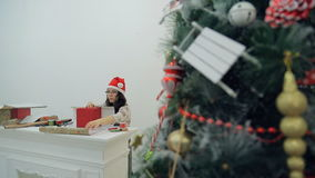 Asian Brunette sitting at the table for Christmas tree gifts packs. Young woman in a red cap and glasses and the face of a large work desk with moldings neatly stock video