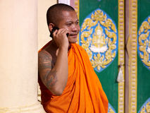 Asian buddhist monk talking on phone in temple. Mid adult buddhist monk speaking with cell phone in monastery, Phnom Penh, Cambodia, Asia Royalty Free Stock Images