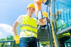 Asian builder with excavator on construction site Stock Images