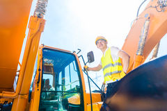 Asian builder in excavator on construction site Royalty Free Stock Photos