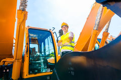Asian builder in excavator on construction site Stock Photos