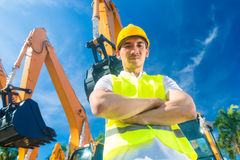Asian builder in front of shovel excavator Royalty Free Stock Image