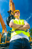 Asian builder in front of shovel excavator Royalty Free Stock Photo