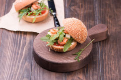 Asian burger with shrimps, arugula, tomato and onion with white sauce royalty free stock photography