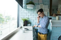 Asian business casual dressed working out of office while standi. Ng in front of the wooden table and computer laptop on and talking on mobile phone and looking Royalty Free Stock Photos