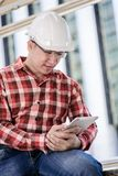 Asian business and engineer man with red scott shirt has planning and working for design buiding and city. stock image