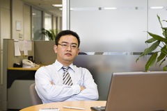 Asian business executive. Asian businessman sitting in office with arms crossed Stock Image