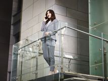 Asian business executive talking on cellphone on top of stairs. Asian corporate executive business woman standing on top of stairs making a call using mobile Royalty Free Stock Photo