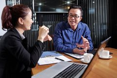 Business executives disucssing new project. Asian business executives disucssing new project at daily meeting royalty free stock photography