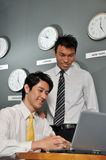 Asian Business Executives In Room Full Of Clocks Stock Photos