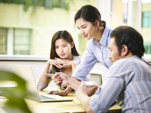 Asian business executives working together in office. A team of young asian corporate executives discussing business in office using laptop computer