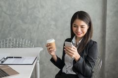 Asian business girl in her workstation at holding coffee cup and. Smartphone while smile Royalty Free Stock Photo