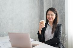 Asian business girl in her workstation at holding coffee cup and. Smile Royalty Free Stock Image
