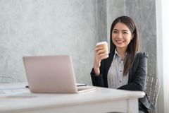 Asian business girl in her workstation at holding coffee cup and. Smile Stock Photo