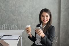 Asian business girl in her workstation at holding coffee cup and. Smartphone while smile Royalty Free Stock Photography