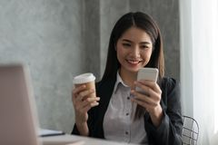 Asian business girl in her workstation at holding coffee cup and. Smartphone while smile Royalty Free Stock Photos