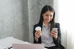 Asian business girl in her workstation at holding coffee cup and. Smartphone while smile Stock Photography