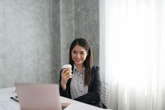 Asian business girl in her workstation at holding coffee cup and. Smile Royalty Free Stock Photography