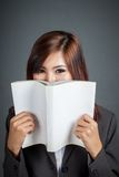 Asian business girl hold a book over her mouth Royalty Free Stock Photo