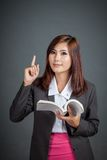 Asian business girl hold a book and point up Royalty Free Stock Image