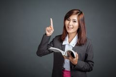 Asian business girl hold a book and point up Royalty Free Stock Photography