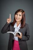 Asian business girl read a book and point up Stock Photo