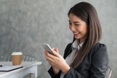 Asian business girl sitting in her workstation while using smart. Phone Royalty Free Stock Image