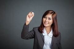 Asian business girl smile write in the air. On gray background Royalty Free Stock Image