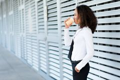 Asian business lady. Drinking coffee outdoors, side view Stock Images