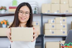 Asian business lady at office. Happy, young, beautiful, Asian business lady, long black hair, wearing eyeglasses, in casual fashion, check delivery tracking royalty free stock photos