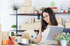 Asian business lady at office. Happy, young, beautiful, Asian business lady, long black hair, wearing eyeglasses, in casual fashion, check delivery tracking royalty free stock images