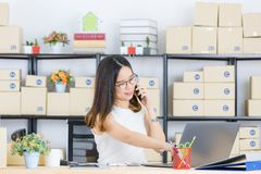 Asian business lady at office. Happy, young, beautiful, Asian business lady, long black hair, wearing eyeglasses, in casual fashion, talking with customer on royalty free stock photography