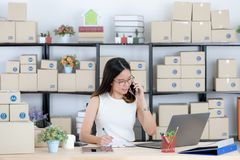 Asian business lady at office. Happy, young, beautiful, Asian business lady, long black hair, wearing eyeglasses, in casual fashion, talking with customer on royalty free stock photo