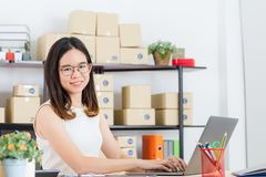 Asian business lady at office. Happy, young, beautiful, Asian business lady, long black hair, wearing eyeglasses, in casual fashion, typing on notebook, sending stock photography