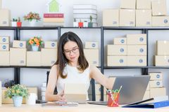 Asian business lady at office. Portrait of young, beautiful, Asian business lady, long black hair, wearing eyeglasses, in casual fashion, check delivery tracking stock photos