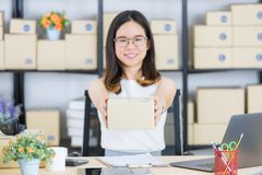 Asian business lady at office. Portrait of young, beautiful, Asian business lady, long black hair, wearing eyeglasses, in casual fashion, smiling, hold out stock images