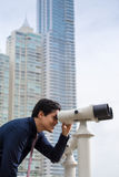 Asian business man with binoculars looking at city Stock Photo