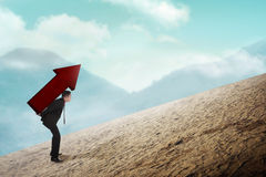 Asian business man carry big red arrow on his back. Business difficulty concept Royalty Free Stock Image