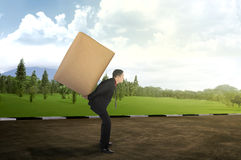 Asian business man carrying brown package on his back Royalty Free Stock Photography