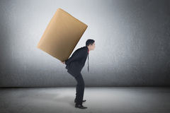 Asian business man carrying brown package on his back Stock Photography