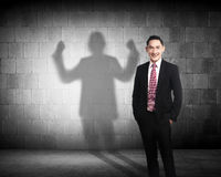 Asian business man casting a strong man shadow stock image