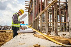 Asian business man construction engineer worker. In protective helmet and blueprints paper on hand measuring concrete floor at house building site Royalty Free Stock Photo