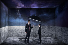 Asian business man covering small version of himself with umbrella Royalty Free Stock Images