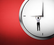 Asian business man hanging on the clock Royalty Free Stock Image