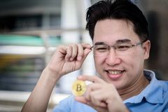 Asian business man has looking on bit coin money with happy. The asian business man has looking on bit coin money with happy Royalty Free Stock Photo