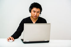 Asian business man with headset. Asian Customer Service Helpdesk Operator Talking To A Customer And Wearing A Headset Behind His Laptop Screen Stock Image