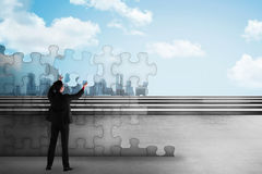 Asian business man holding piece of puzzle trying to build a city. Business development concept Stock Image