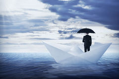 Asian business man holding umbrella standing on the paper boat Royalty Free Stock Photography
