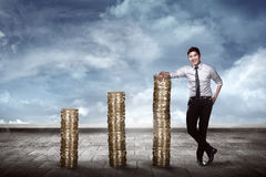 Asian business man leaning on the pile of coins Stock Images