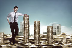 Asian business man leaning on the pile of coins Stock Image